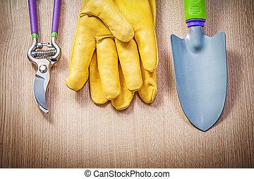 Safety gloves hand shovel garden pruner on wood board gardening