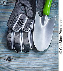 Safety gloves hand shovel on wooden board gardening concept