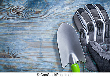 Safety gloves hand spade on wooden board gardening concept