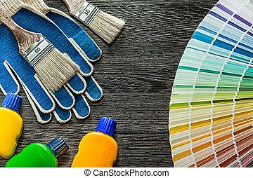 Safety gloves paint brushes bottles pantone fan on wooden board