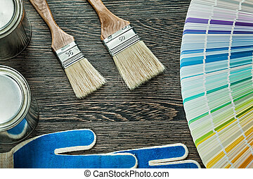 Safety gloves paint brushes cans pantone fan on wooden board