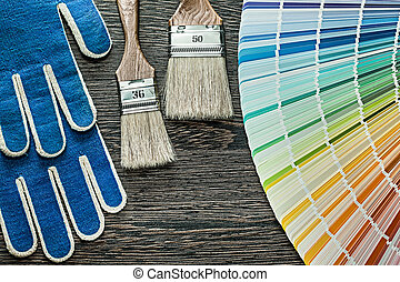 Safety gloves paint brushes pantone fan on wooden board