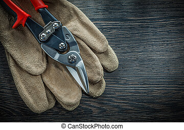 Safety gloves steel cutter on wooden board.