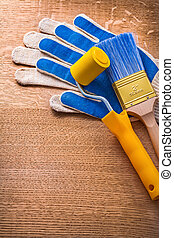 Safety gloves with paint roller and brush on wooden board constr