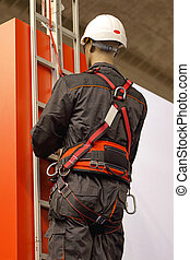 Safety harness - Worker on a ladder uses a safety harness to...