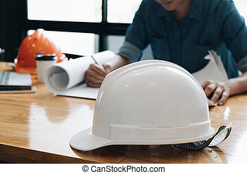 Safety helm with Yong architect man working with blueprints, yong engineer inspection in workplace for architectural plan project,sketching a construction project ,Business concept