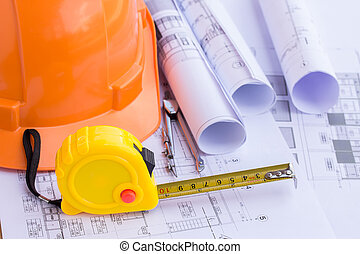 Safety helmet and tape measure over a construction plan