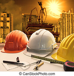 safety helmet on architect ,engineer working table with modern building and crane construction background use for construction business and civil engineering ,real estate topic