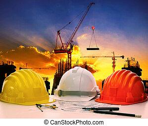 safety helmet on civil engineer working table against crane...