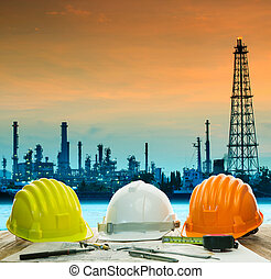 safety helmet on engineer working table against beautiful oil re