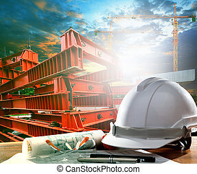 safety helmet on engineer working table against crane and road c