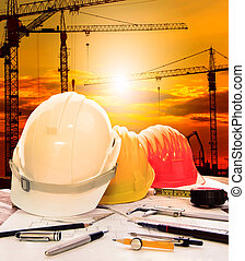 safety helmet on engineer working table and construction site background