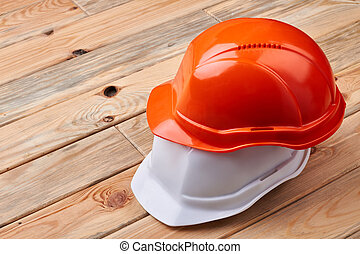 Safety helmets on wooden background.