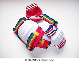 Safety pads - Elbow and knee pads in a pile over a white...