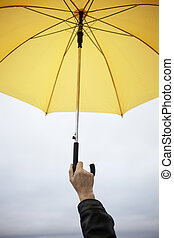 safety - hand of man with yellow umbrella, selective focus...