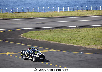 Safety vehicle on an airport runaway near the ocean. Azores