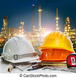 safey helmet on engineer working table agaisnt beautiful lighting of oil refinery in petroleum petrochemical plant use for energy ,power and fossil fuel industry