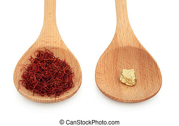 Saffron spice and gold nugget in wooden spoons over white background. Gram for gram equal value.