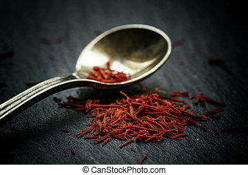 Saffron in a spoon on a dark background, selective focus, macro shot, shallow depth of field