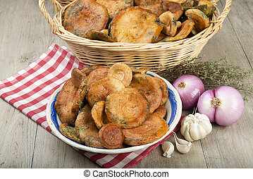 Saffron milk caps or red pine mushrooms in baskets and bowls on the kitchen table