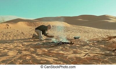 sahara man cooking bread - a man camping in the sahara...