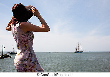 Women with summer hat waving hand to ship sailing out of the port