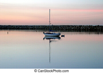 Sail Boat #1 - A sail boat sits in a harbor during sunset,...