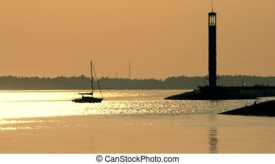 Sail boat enters a harbor at dusk near lighthouse
