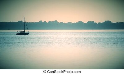 Sail boat far off on a lake or river