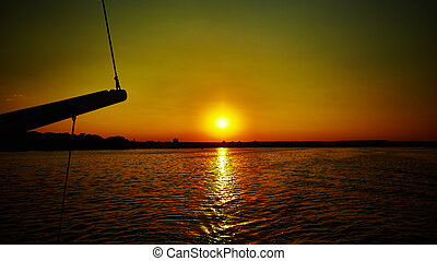 Sail boat gliding in sea at sunset