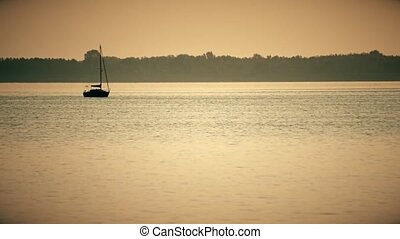 Sail boat silhouette far off on a lake or river in the...