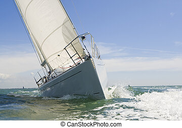A beautiful white yachts racing close to the camera on a bright sunny day