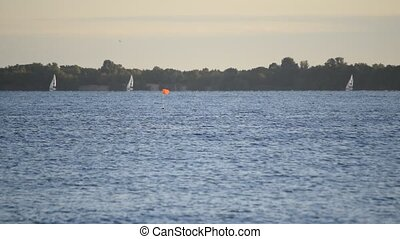 Sail boats far off on a lake or river with blue water