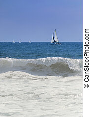 Sail boats at sea with crashing wave in foreground.