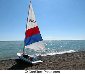 Sailboat - A small sailboat, pulled up onto the beach on a ...