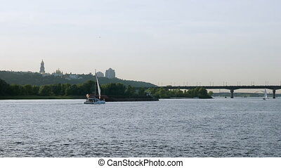 Sailboat and barge float on the summer Dnieper river in the Kiev city.