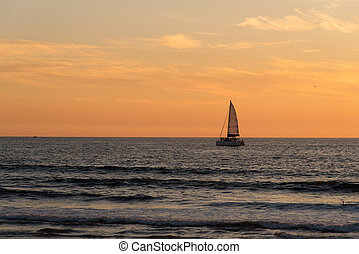 Sailboat at sunset in the Pacific Ocean