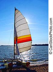 Sailboat backlit - Catamaran on a beach with backlit sail