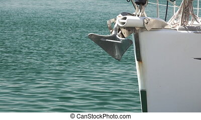 Sailboat bow moored with rope and anchor, focus on foreground