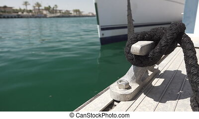 Sailboat bow moored with rope, focus on foreground - Detail...