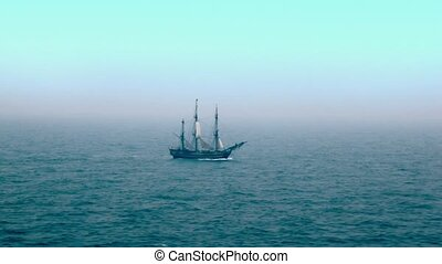 Sailboat floats by wavy sea surface far away under blue sky