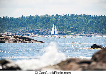 Sailboat cruising thru archipelago with watersplash in the foreground, Sweden