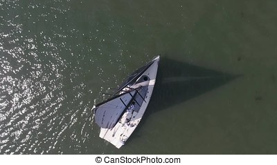 Sailboat in the sea near the port. Footage. White sailboat in the sea