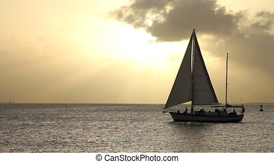 Sailboat Key West Sunset - Silhouetted sailboat moves across...