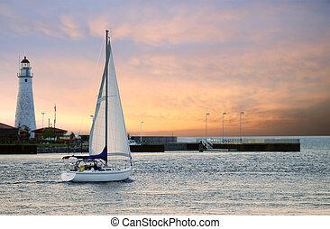 sailboat leaving marina with setting sun