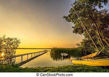 Sailboat on a lake with reeds at sunrise