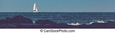 Sailboat on Atlantic Ocean - A catamaran sailboat sails past...