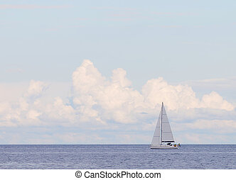 Sailboat on the glittering blue sea, large clouds