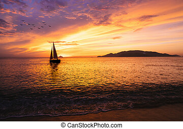 Sailboat on the ocean at sunrise