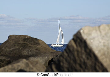 Sailboat on the Rocks - A sailboat framed by soe rocks.